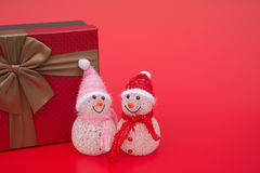 Two smiling toy christmas snowman and a present box on red background Royalty Free Stock Image