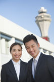Two Smiling travelers portrait at airport Stock Photos