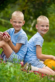 Two smiling twin brothers holding fruits Stock Photos
