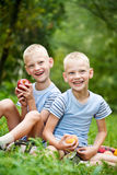 Two smiling twin brothers holding fruits Royalty Free Stock Photos
