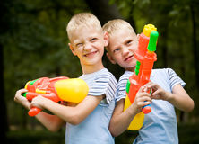 Two smiling twin brothers with water guns Stock Image