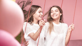 Two smiling twins female models posing. Two beautiful young caucasian girls posing close together with amazing toothy smiles.Twins sisters enyoing time together Stock Photos