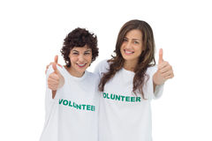 Two smiling volunteers giving thumbs up Stock Image