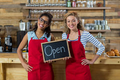 Two smiling waitress standing with open signboard in cafe Royalty Free Stock Photo