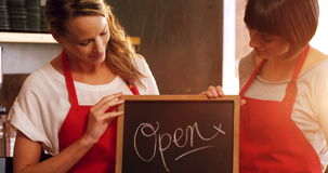 Two smiling waitresses holding a open sign board. In cafe 4k stock video footage