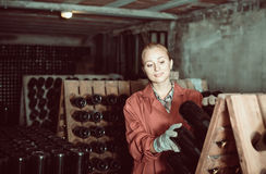 Two smiling winery employees in aging section in cellar Royalty Free Stock Images