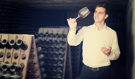 Two smiling winery employees in aging section in cellar Stock Photography