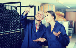 Two smiling winery workers different ages in aging section of fa Stock Photos