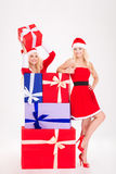 Two smiling woman in santa cloth standing with present boxes Stock Photography