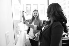 Two Smiling Woman Writing on Board Stock Photo