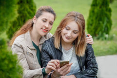 Two smiling women friends sharing social media in smart phone. Outdoors Stock Photo
