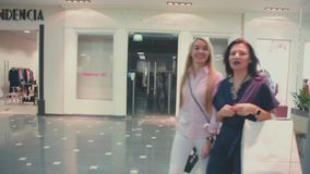 Two smiling women go in the store. Two friends go shopping. stock video
