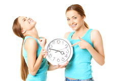 Two smiling women holding a clock Royalty Free Stock Photo