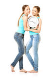 Two smiling women holding a clock. Isolated over a white background stock photos