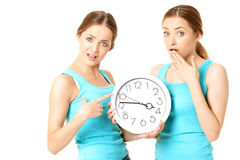 Two smiling women holding a clock. Isolated over a white background Royalty Free Stock Photo