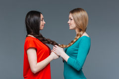 Two smiling women holding hands and looking on each other Stock Photos