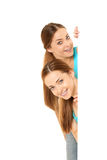 Two smiling women holding white blank poster Stock Images