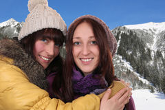 Two smiling women hug each other in the mountains Royalty Free Stock Images