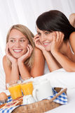 Two smiling women lying down having breakfast Royalty Free Stock Photography