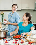 Two smiling women making perogies with berries Stock Photography