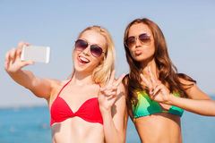 Two smiling women making selfie on beach Stock Images