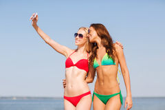 Two smiling women making selfie on beach Stock Photos
