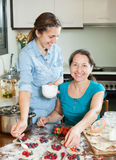 Two smiling women making  vareniki with berries Royalty Free Stock Photography