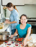 Two smiling women making  vareniki with berries Royalty Free Stock Photo