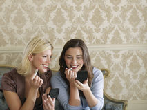 Two Smiling Women Putting On Makeup Royalty Free Stock Photos