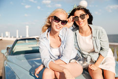 Two smiling women sitting on the car hood in summer Stock Photo