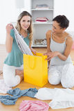 Two smiling women sitting on floor with shopping bag Stock Photo