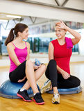 Two smiling women sitting on the half balls Royalty Free Stock Photography