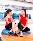 Two smiling women sitting on the half balls Royalty Free Stock Images
