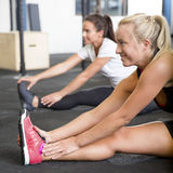 Two smiling women stretching on the floor Royalty Free Stock Images
