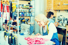 Two smiling women tailors different ages working with sewing mac. Hines at studio stock image
