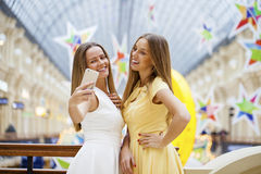 Two smiling women take a picture of herself with a smart phone Stock Photos