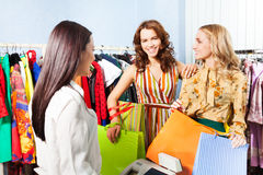 Two smiling women talking with shop assistant Stock Images