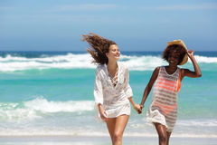 Two smiling women walking together at the seaside Royalty Free Stock Photo