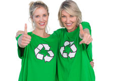 Two smiling women wearing green recycling tshirts giving thumbs up Stock Image