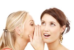 Two smiling women whispering gossip. Friendship, happiness and people concept - two smiling women whispering gossip royalty free stock photography