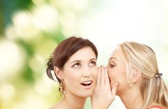Two smiling women whispering gossip. Friendship, happiness and people concept - two smiling women whispering gossip royalty free stock photo
