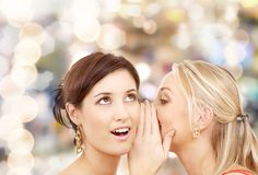 Two smiling women whispering gossip Stock Image