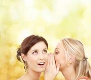 Two smiling women whispering gossip Stock Photos