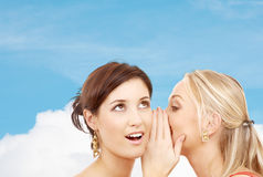 Two smiling women whispering gossip Stock Photo