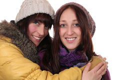 Two smiling women in winter clothing hug each other Royalty Free Stock Image