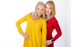 Two smiling women in yellow and red dresses Royalty Free Stock Images
