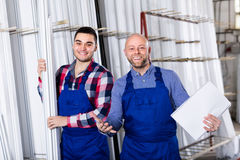 Two smiling workmen at factory. Cheerful workmen enjoying of production plan overfulfilment at factory royalty free stock photography
