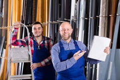 Two smiling workmen at factory. Two smiling workmen enjoying of production plan overfulfilment at factory stock images