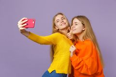 Two smiling young blonde twins sisters girls in colorful clothes doing selfie shot on mobile phone  on pastel stock image