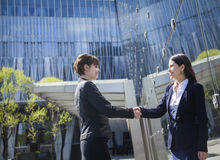 Two smiling young businesswomen shaking hands outdoors in Beijing, China Stock Images
